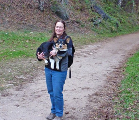 Linda carries Ranger the Corgi on the trail.